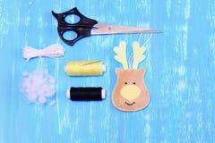 如何做毛毡圣诞节鹿装饰品 步骤 灰棕色感觉鹿顶头装饰品,剪刀,螺纹,针,绳子,补白 库存图片
