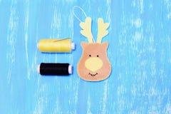如何做毛毡圣诞节鹿装饰品 步骤 灰棕色感觉鹿顶头装饰品,螺纹,在蓝色木背景隔绝的针 免版税库存照片