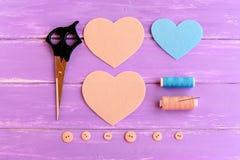 如何创造毛毡心脏工艺 步骤 蓝色和灰棕色毛毡片断切开了以心脏的形式 剪刀,螺纹,按钮,针 免版税库存图片