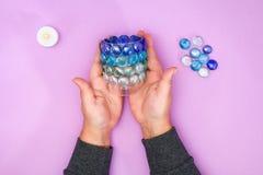 如何由多余的玻璃或塑料和玻璃小卵石做您自己的烛台 逐步 圣诞节内部装饰 图库摄影