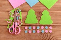 如何缝合圣诞节装饰 步骤 毛毡圣诞树样式,毛毡小块,在木背景的剪刀 免版税库存照片