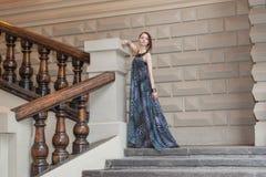 如纱的长的礼服的迷人的肉欲的少妇在台阶 免版税库存照片