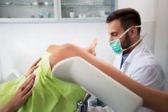 年轻妇产科医师检查他的诊所的患者 库存图片