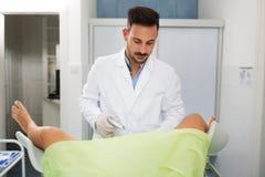 年轻妇产科医师检查他的诊所的患者 免版税图库摄影