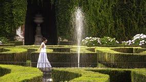 年轻贵妇人在一个美妙的庭院里 影视素材