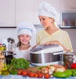 主妇和女儿有crockpot的在厨房 库存照片