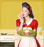 年轻主妇在她的手上的拿着甜杯形蛋糕 减速火箭的海报 库存图片