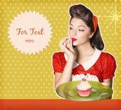 主妇在她的手上的拿着甜杯形蛋糕 减速火箭的海报backgr 免版税图库摄影