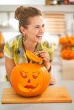 主妇在有一个大橙色南瓜杰克O灯笼的厨房里 免版税库存图片