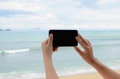 妇女'拍与手机的s手照片 库存图片