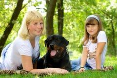 妇女、女孩和狗在草。 免版税库存图片