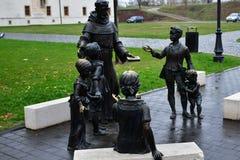 妇女、教士和孩子古铜色雕象  免版税库存图片