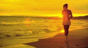 妇女、波浪和日落的艺术图片 库存图片