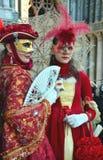 妇女一对未认出的夫妇穿戴与面具、白色手套、珠宝和帽子的精心制作的红色华丽服装有红色羽毛的 库存照片