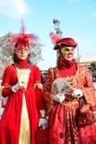 妇女一对未认出的夫妇穿戴与面具、白色手套、珠宝和帽子的精心制作的红色华丽服装有红色羽毛durin的 库存图片