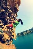 妇女上升在海边山岩石墙壁的攀岩运动员 图库摄影