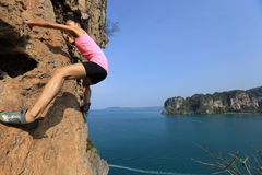妇女上升在海边山岩石的攀岩运动员 库存照片