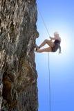 妇女上升的岩石 免版税图库摄影
