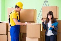 妇女上司和人承包商与箱子交付一起使用 免版税库存图片
