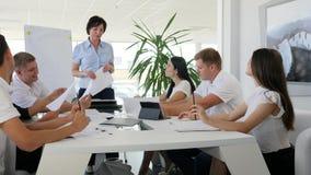 妇女上司藏品与在大白色桌后的年轻合作者回面到现代会议室里 股票视频