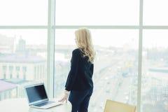妇女上司运转的办公室膝上型计算机递样式 免版税库存照片