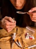 妇女上瘾者麻醉用途的海洛因 有匙子的吸毒者烹调药物的 免版税库存照片