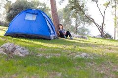 妇女下个蓝色帐篷 库存图片