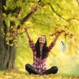 妇女下落叶子在秋天公园 库存照片