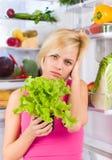 妇女不快乐的菜沙拉饮食,冰箱 免版税库存照片