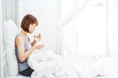 妇女不是在床垫的舒适的吃药片 免版税库存图片