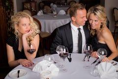 妇女不耐烦,当吃与夫妇时的晚餐 免版税库存照片