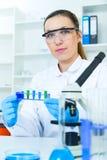 妇女与一个显微镜一起使用在实验室,在研究员的眼睛的透镜焦点 图库摄影