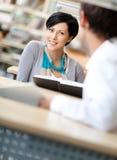 妇女与人沟通在图书馆 免版税库存图片