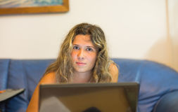 妇女与便携式计算机一起使用在晚上 免版税图库摄影