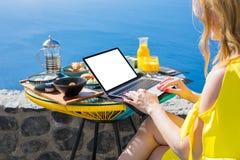 妇女与便携式计算机一起使用,当食用在大阳台时的早餐 免版税库存照片