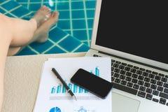 妇女与便携式计算机和财政文件一起使用 免版税库存照片