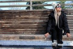 妇女与冬天穿衣,坐与雪的一个长木凳 免版税库存照片