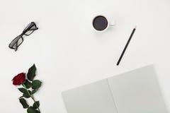 妇女与咖啡的工作空间、铅笔、空的笔记本、镜片和玫瑰色花在白色桌上从上面 平的位置 免版税库存照片