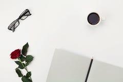 妇女与咖啡的工作空间、铅笔、空的笔记本、玻璃和玫瑰色花在白色桌上从上面 平的位置 免版税库存照片