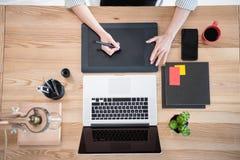 妇女与图画片剂和膝上型计算机一起使用在桌面 图库摄影