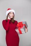 妇女与圣诞节帽子举行礼物讲电话 图库摄影