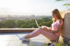 妇女与在大阳台俯视的城市的膝上型计算机一起使用 图库摄影