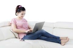 妇女与在舒适沙发的膝上型计算机一起使用 免版税库存图片