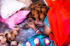 妇女与在街道上的陶瓷一起使用。 免版税图库摄影
