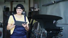 妇女与在车库的一种数字式片剂一起使用汽车修理的 影视素材