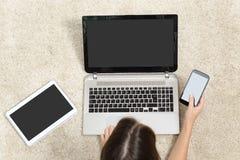 妇女与多个设备屏幕一起使用 库存照片
