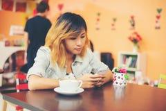 妇女与她的机动性的正文消息特写镜头在咖啡店 库存照片