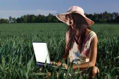 妇女与室外的膝上型计算机一起使用 库存图片