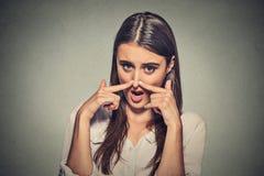 妇女与手指手神色的少量鼻子充满憎恶某事发恶臭 免版税库存照片
