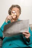 妇女与放大镜的读书报纸 库存图片